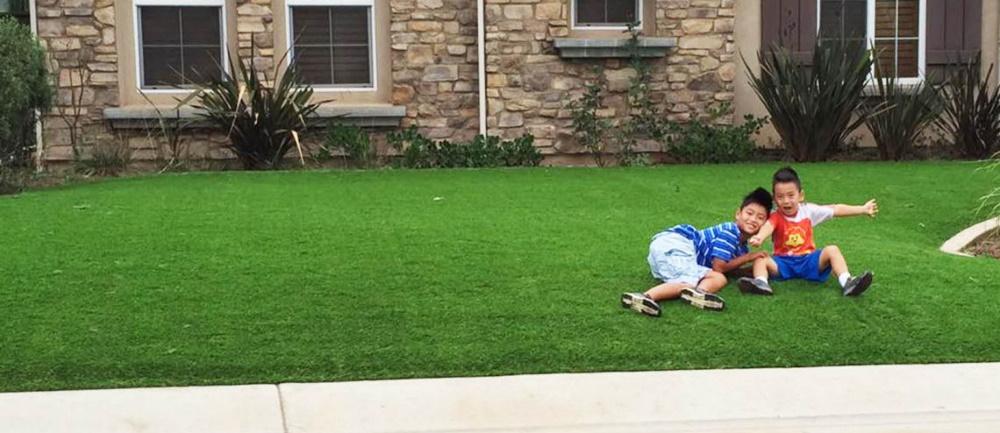 Spelende kinderen op een grastapijt in de voortuin