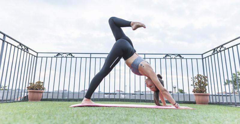 Yoga op een balkon op kunstgras